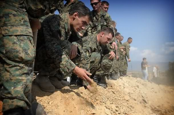 Georgian soldiers throw earth on the mass grave for unknown Georgian soldiers killed in South Ossetia in 2008