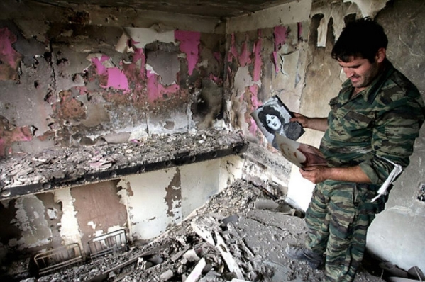 Soldier holds pictures of his family in Tskhinvali apartment