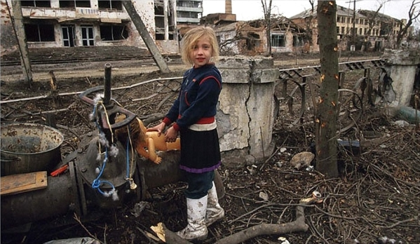 "Mark Irkali on Grozny, 2002 - ""Some little girl had a little paper doll, something that someone made for her. He asked what it was and she held it up, but it dropped, and it fell into a hole where the street has been blown clear down to the sewer. He was down on his knees looking for it. Then he's trying to squeeze down to climb into the sewer and get it."