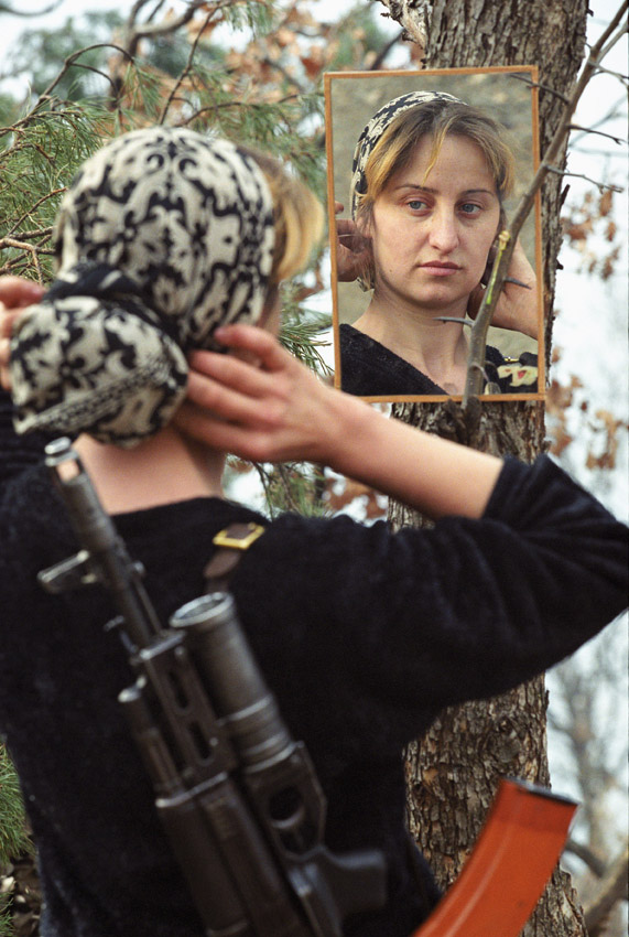 Chechnya, Russia, Chechen insurgents' wife arrangers her scarf on a mountain base. Chechen women fighting in war was common until radical Islam took over and they were excluded from all activities.