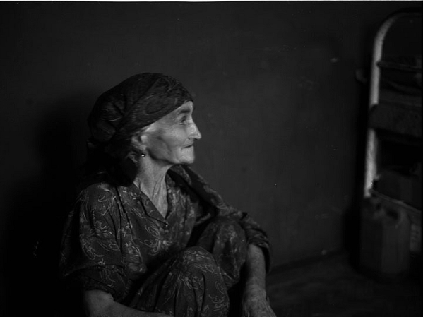 An elderly refugee from southern Chechnya's Itum-Kale district sits in the home of a Kist host family in Duisi, Georgia. I was struck by how incredibly hospitable these people relentlessly vilified by the FSB were. They told me of the horrors of Putin's onslaught on their villages while offering endless cups of tea and bread me. I felt powerless, having nothing to givein return  but a sympathetic ear. ©2002 Derek Henry Flood
