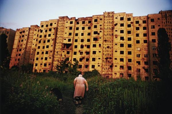 "Babushka ""Tanya,"" an elderly ethnic Russian woman, heads back to her bombed out apartment building after walking her dog. Despite the damages, three apartments remain occupied in the building"