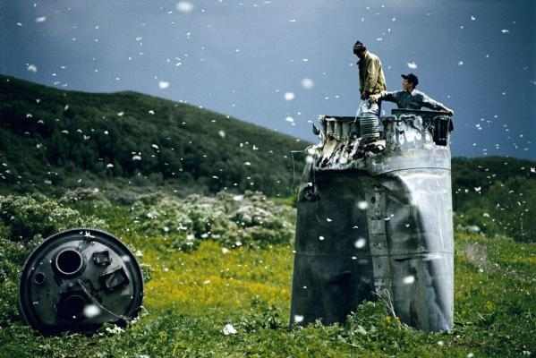 Kazakhstan Villagers collecting scrap from a crashed spacecraft, surrounded by thousands of white butterflies. Environmentalists fear for the region's future due to the toxic rocket fuel.