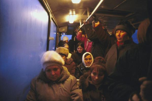 People on a bus commuting to a factory in the cold winter morning.