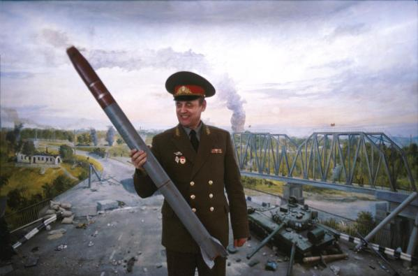 Transdniesterian deputy minister of defense looking lovingly at an Alazan missile in front of a scene from 1992 breakaway war with Moldova. The Alazan missile has been in the media's focus as of late, with a Washington Post article accusing Transdniester of lacing the small missiles with nuclear dirty bomb warheads, something the government strongly denies. 2004