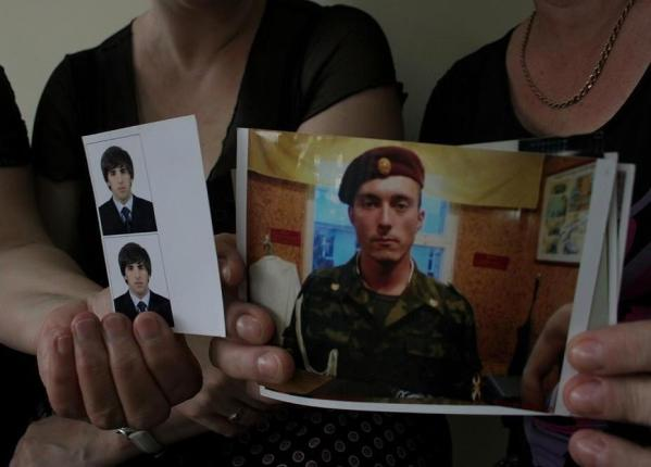 "From left to right: Zhanna Ismailova is showing a picture of her youngest son, Rashid Ismailov, 26, who was abducted on May 8, 2012. Wwitnesses saw him being dragged away by men in black uniforms. Oksana and Burliyat Danilin are showing pictures of their husband and son Timur Danilin, 35, abducted on March 24, 2012. Timur managed to call his wife's cell and say: ""Please save me from here."" Those were the last words she heard from him. Image by Anna Nemtsova. Russia, 2012."